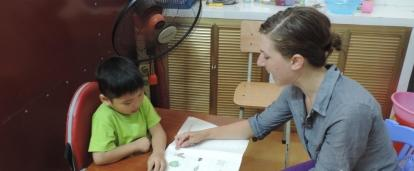 A Projects Abroad intern is seen helping a young boy read during her speech therapy internship in Vietnam.